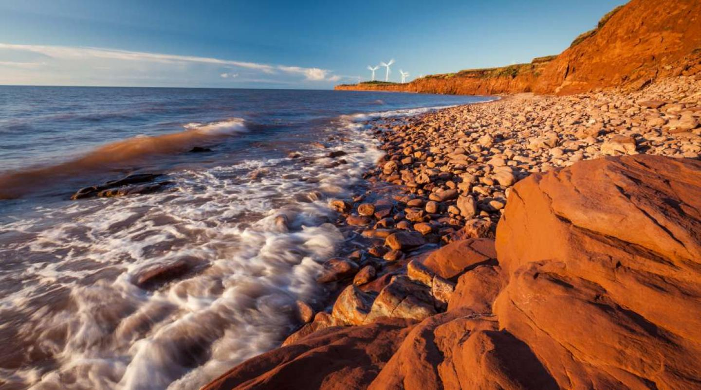 Image of PEI beach with red cliffs and wind turbines in background