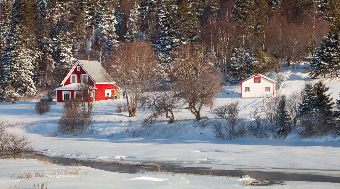 Beauty shot of red house and barn with white trim with snow-covered trees in background and and fields