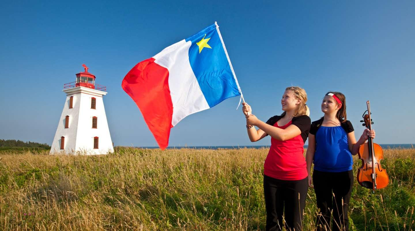 Two young Acadian girls stand in a summer field with lighthouse in background. One is holiding the Acadian flag with the other holiding a fiddle