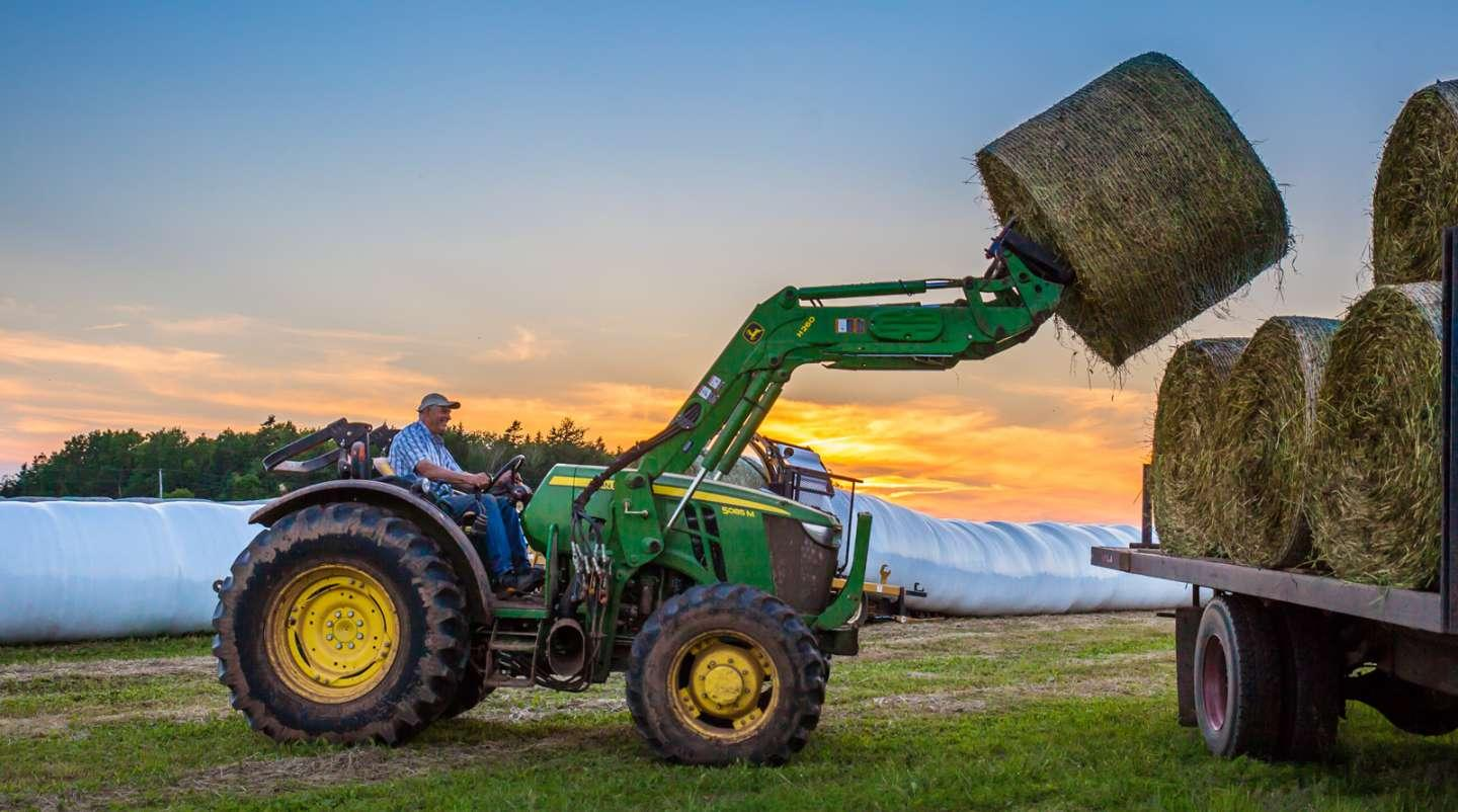 Farmer on John Deere tractor using front end loader to lift round bales onto wagon at sunset