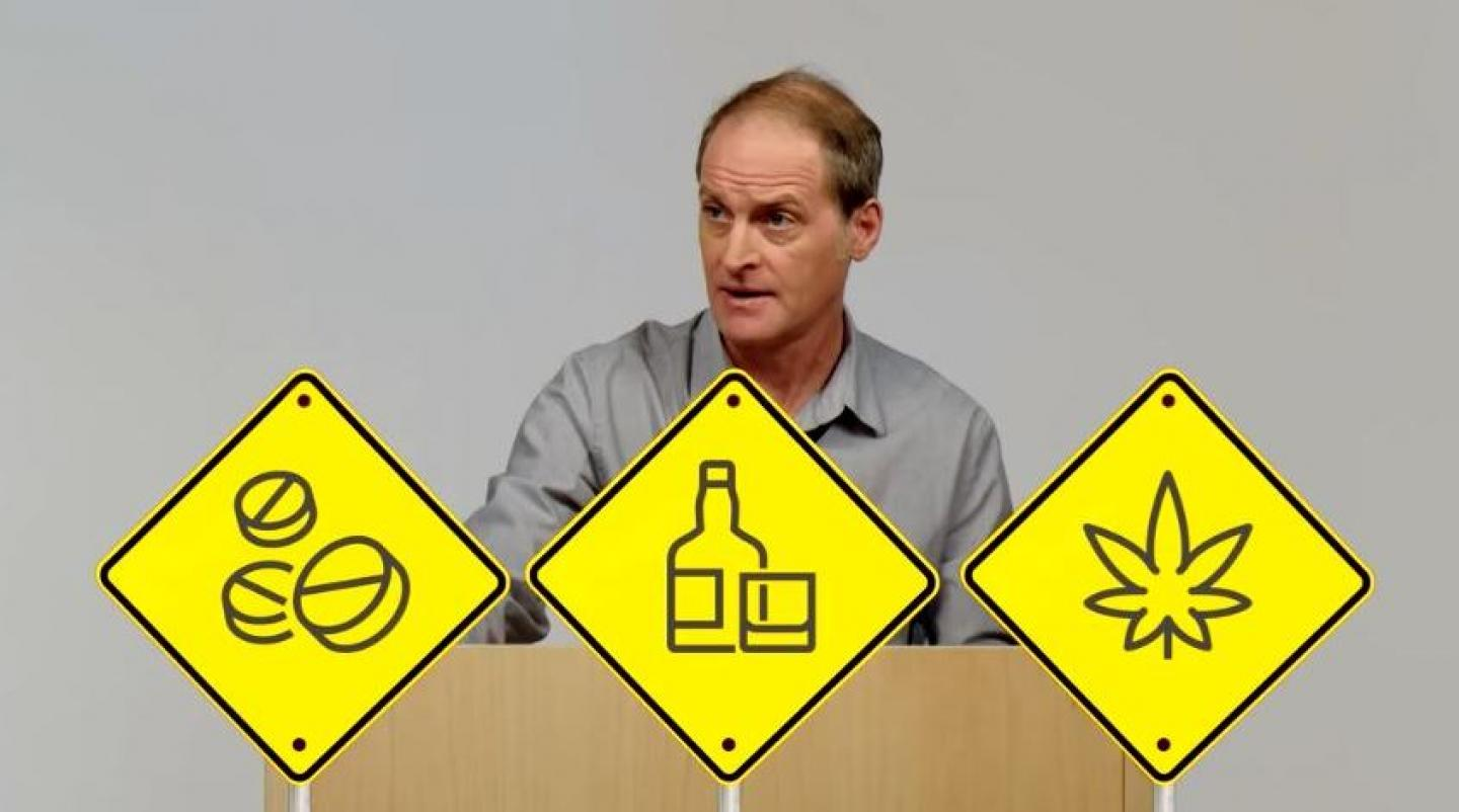 Man standing at a podium with traffic signs in front of him