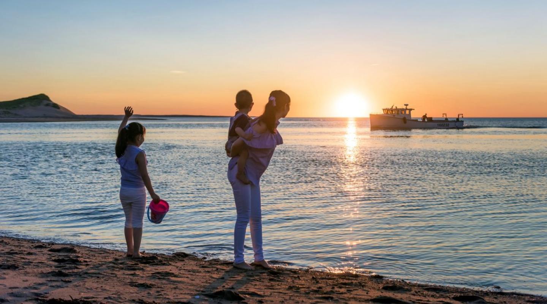 Image of family of three watching sunset on PEI beach