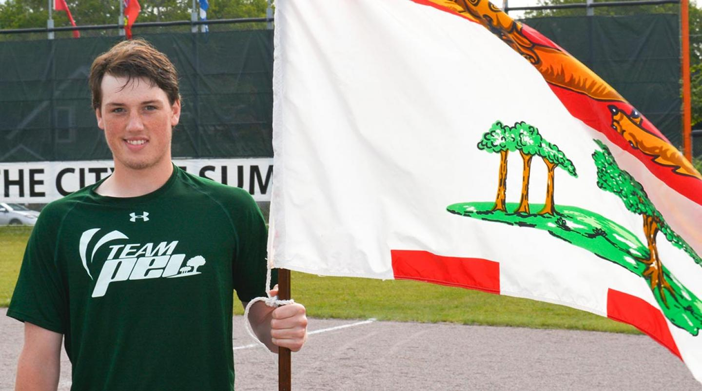 Male athlete of Team PEI holds PEI flag for Canada Games