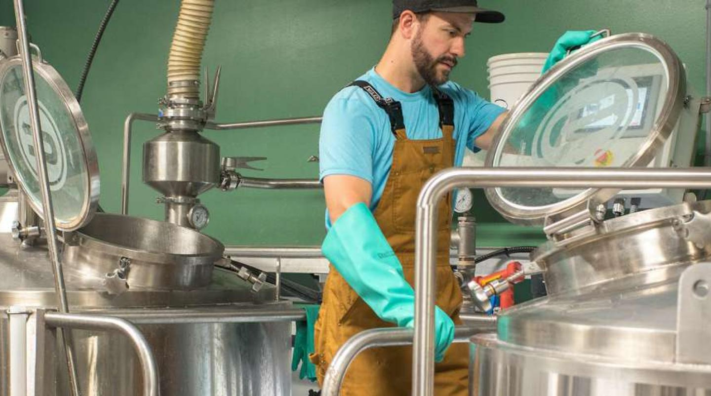Image of male employee working in micro brewery with DME kettles