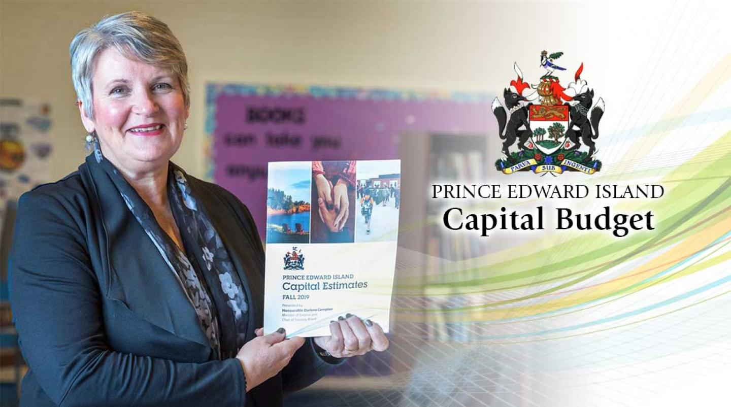 Hon. Darlene Compton, PEI Minister of Finance, holds up a copy of the capital budget for 2020-21. She is in an Island classroom.