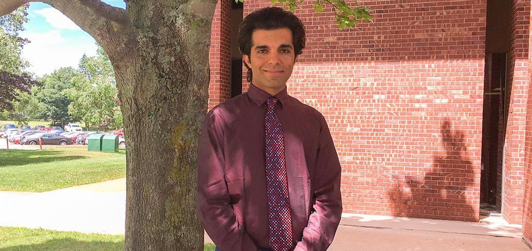Ali Siadat stands next to a tree outdoors