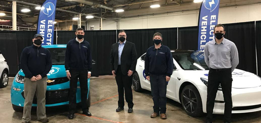 Four Electric Vehicle reps stand in front of two electric vehicles in a convention facility