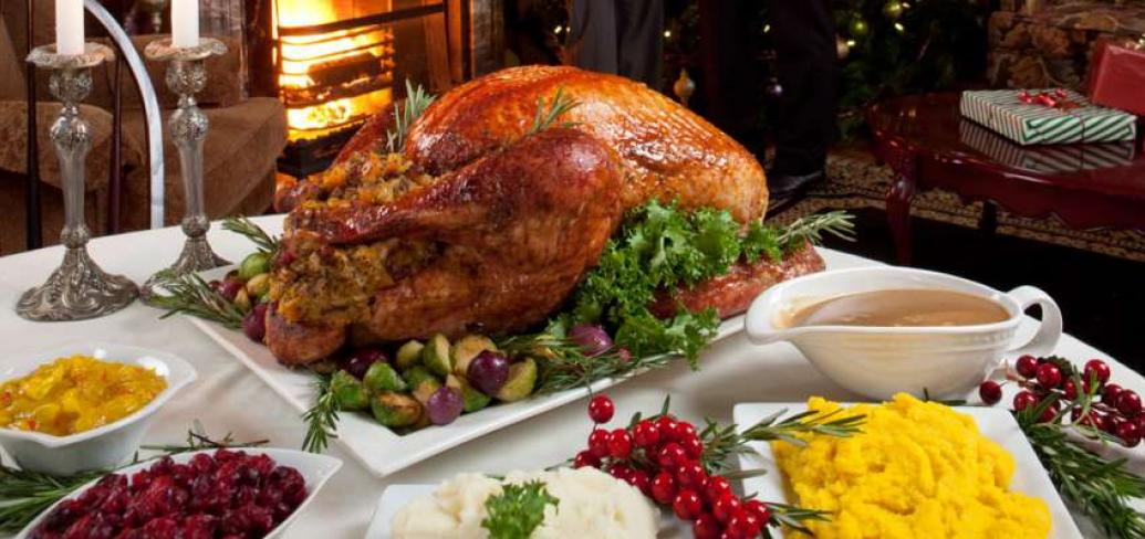 Image of dinner table set with roasted turkey, mashed potatoes, cranberry sauce and pickles