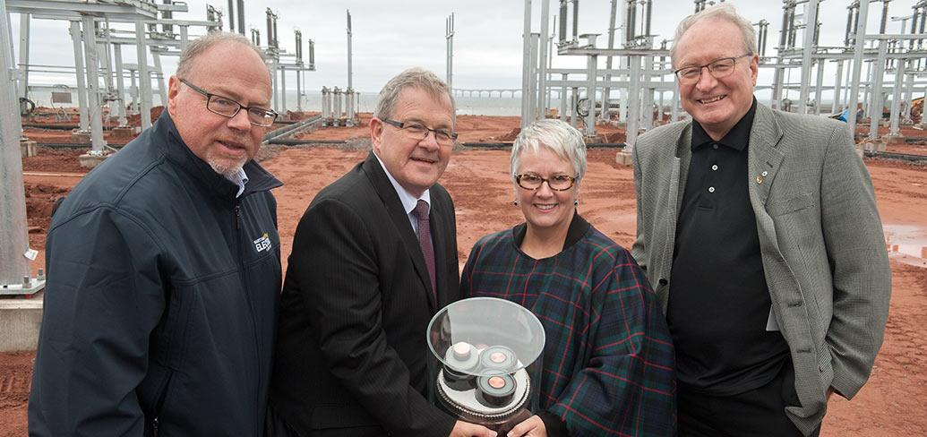 Four people holding underwater cable sample at Borden electric substation.