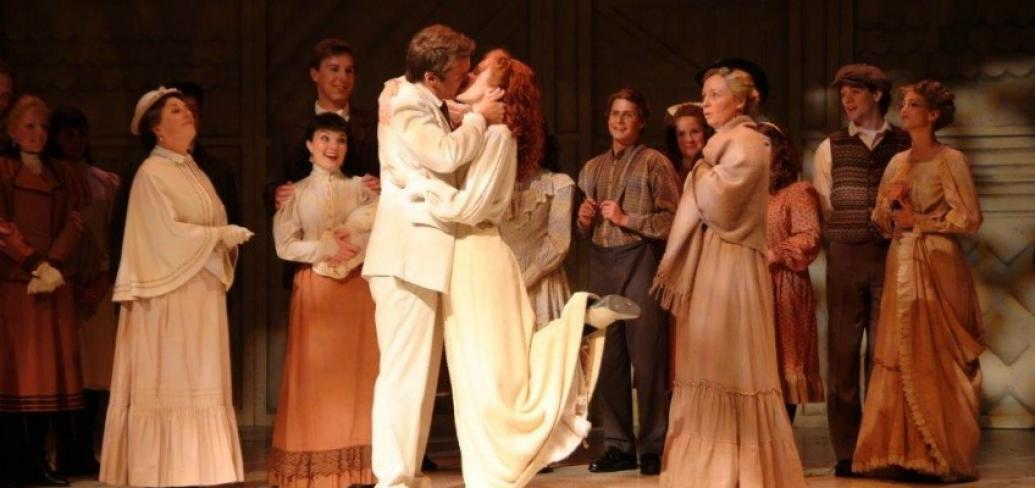In a scene from Anne & Gilbert the Musical, Anne and Gilbert share a kiss while the towns people look on.