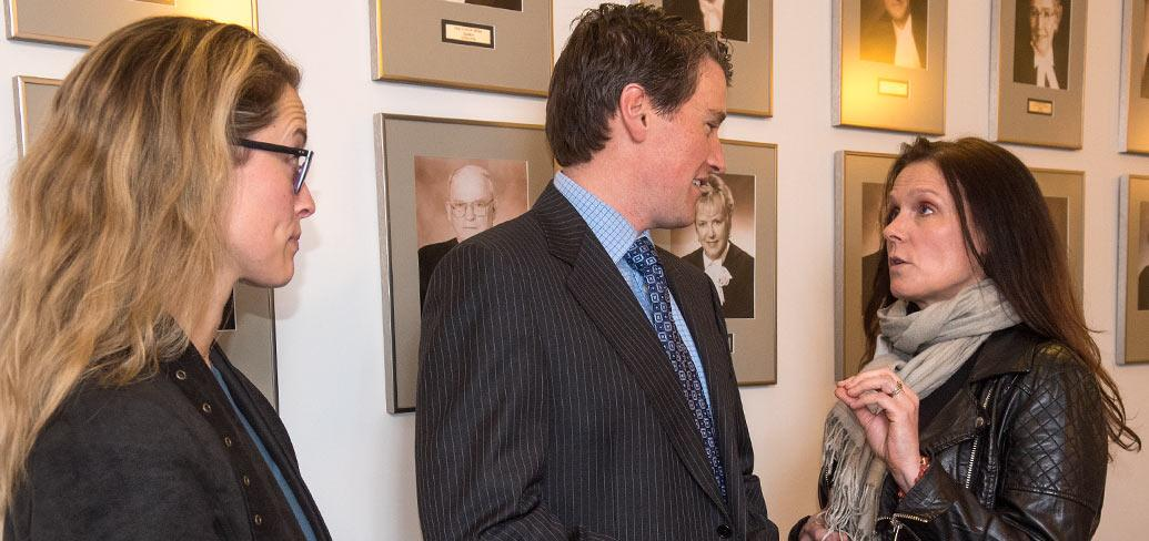 Photo shows two women talking with Minister Jordan Brown