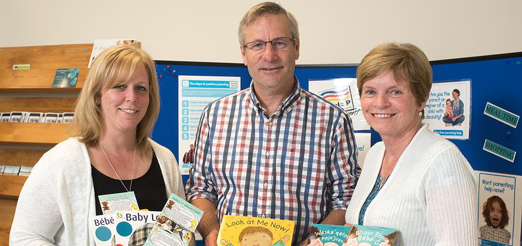 Three people standing together displaying baby books