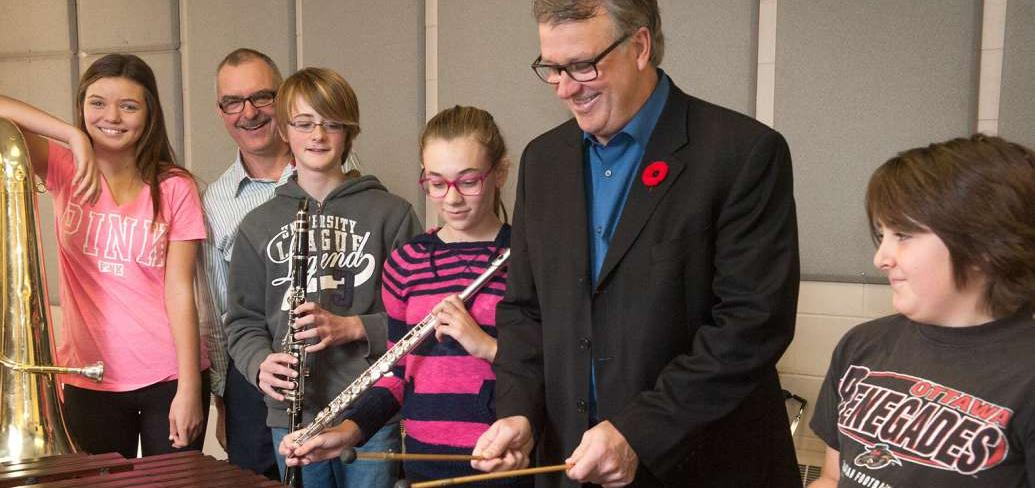 Minister Doung Curie and Music Teacher Frank Nabburs and four students hold musical instruments