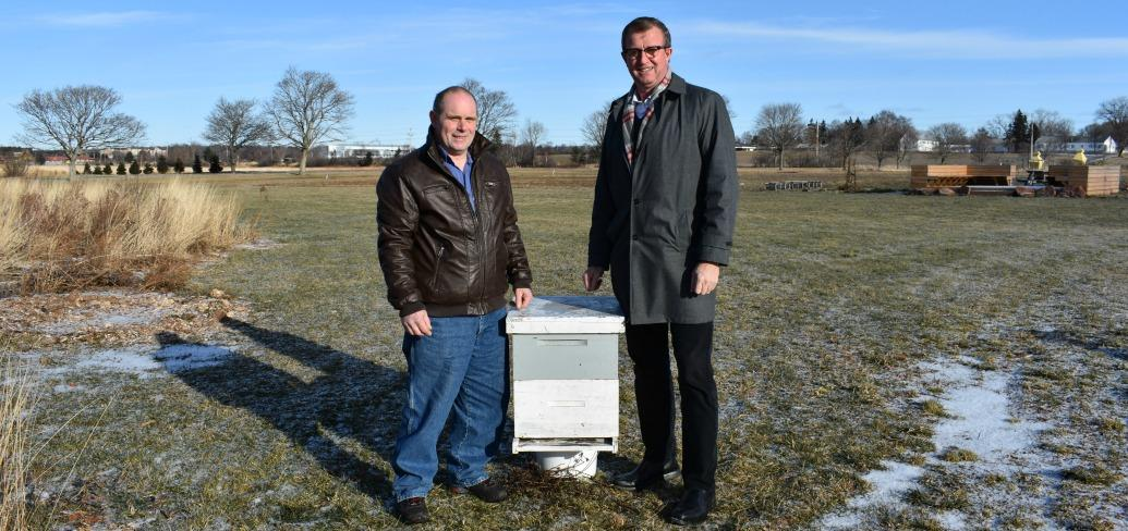 Photo shows two men standing on either side of a box-shaped beehive.