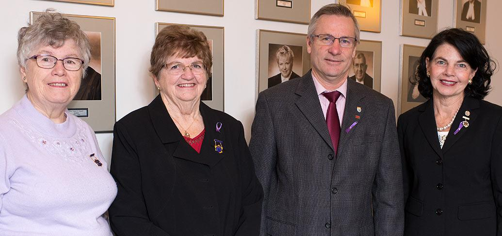 Photos shows Minister Robert Henderson standing with three women.