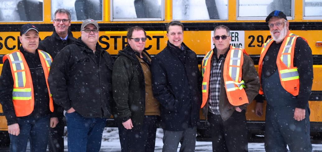 Minister Trivers and PSB Director Parker Grimmer stand outside beside a bus with school bus driver training participants