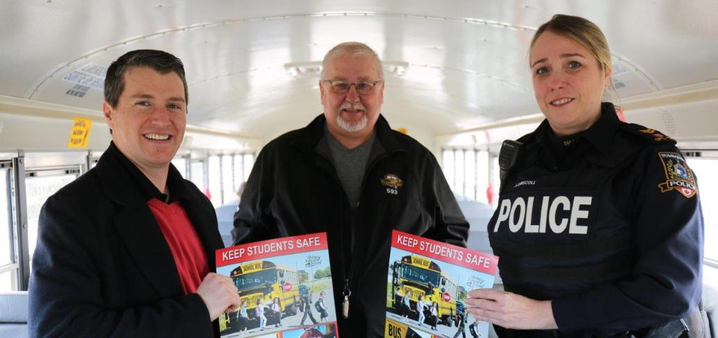 Three people stand inside a school bus holding school bus safety posters