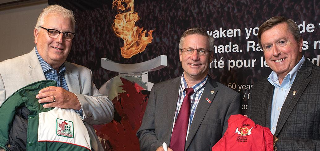 Brian McFeely holds a 1991 Canada Games jacket, Health and Wellness Minister Robert Henderson and Wayne Carew hold a 2009 Canada Games jacket at announcement