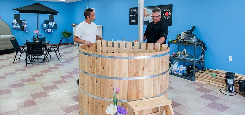(L to R): Blaine Richards, owner and operator of Richards Total Pool Services shows Minister Heath MacDonald, Economic Development and Tourism an Island-made cedar hot tub. The new cedar tubs are a one-of-a-kind product now available on PEI