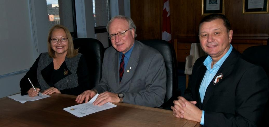 Chief Matilda Ramjattan, Premier Wade MacLauchlan and Chief Brian Francis sit at a table smiling at the camera.