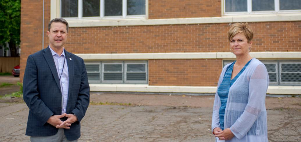 Image of two people standing in fromt of a brick building