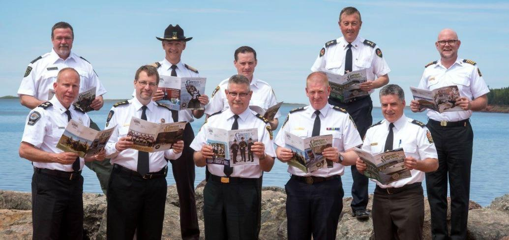 Photo of 10 Conservation Officers from across the country, standing in front of the water at Greenwich National Park, holding maps og the park