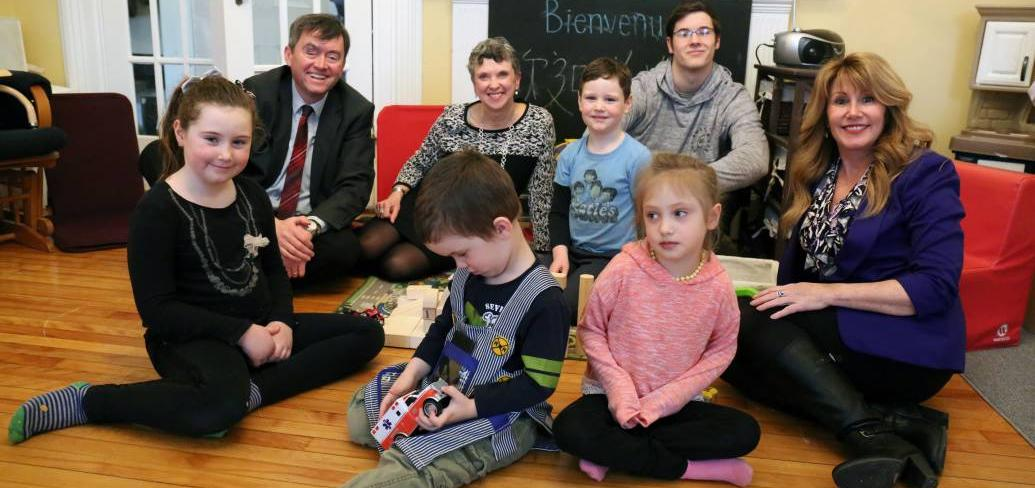 Minister Mundy sits with people in front of a non-working fireplace