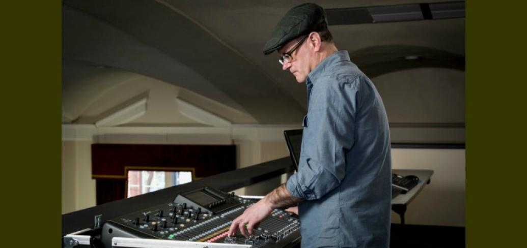Music composer Craig Dodge is shown in this photo standing at a sound board