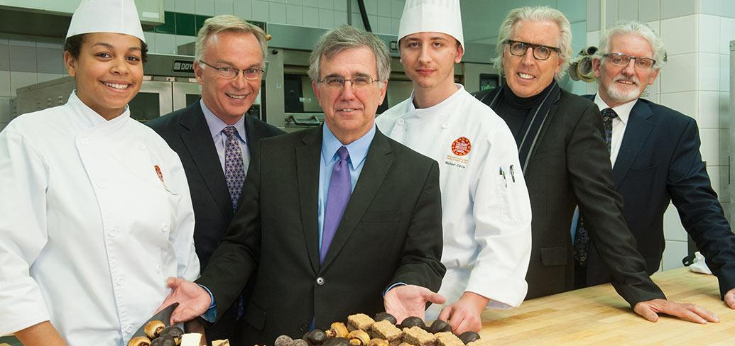 Minister Brown and five other people at a table display a tray of desserts
