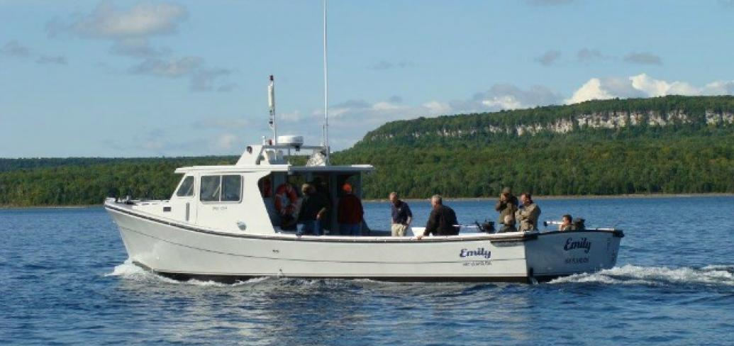 A boat, built by Provincial Boat and Marine Ltd, sails on clear blue water on a beautiful summer day.