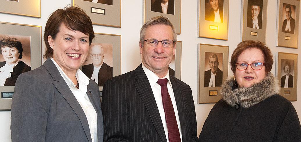 Photo shows three individuals standing side by side
