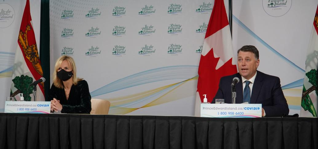 image of two people wearing masks while sitting at a news conference table