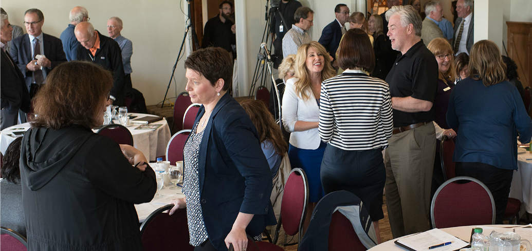 A group of people stand talking informally at the recent Economic Forum