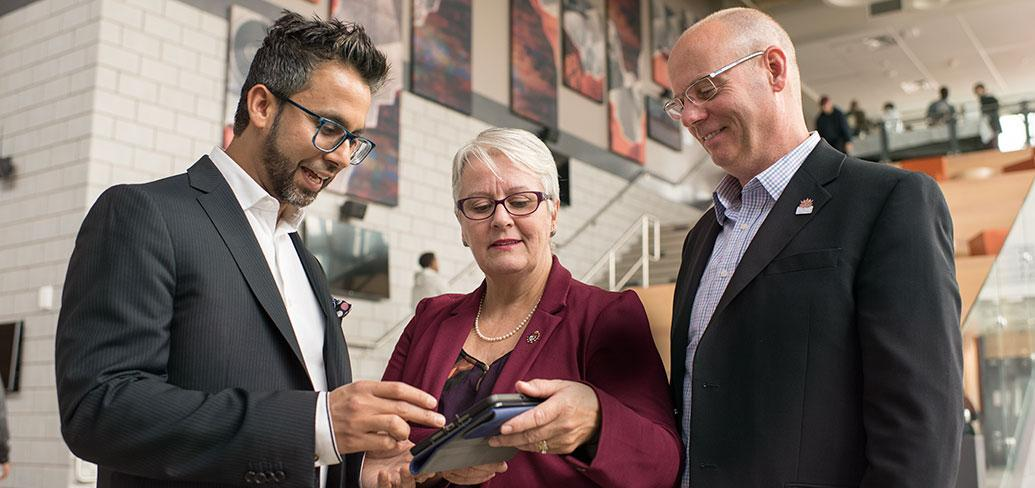 Photo shows three people looking at an app on a tablet