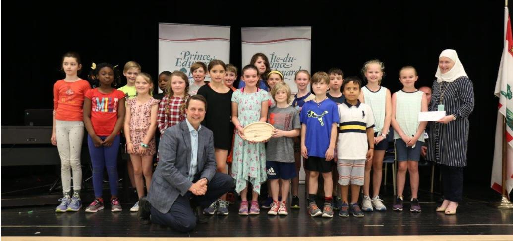 Minister Brad Trivers kneels in front of a group of children from Spring Park School's Grade 4C French Immersion class