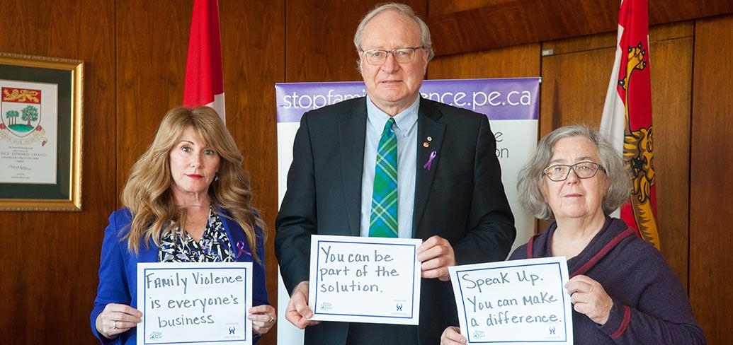 Three people holding signs reminding us to speak out against family violence