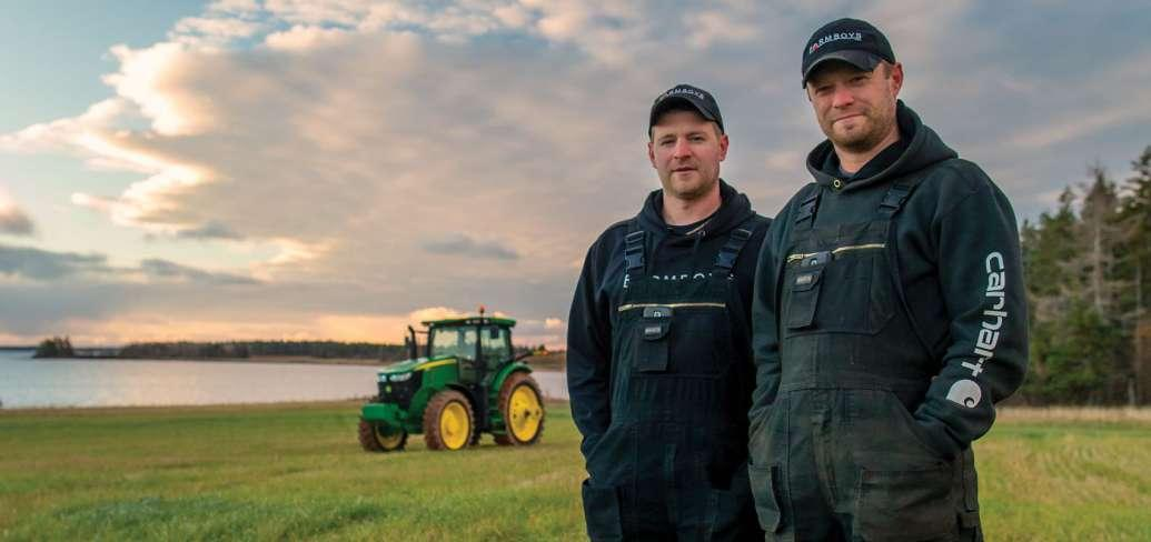 Brothers Bryan and Kyle Maynard of Arlington stand in field with tractor in background