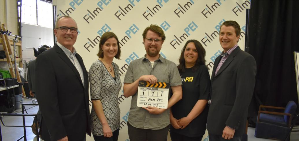 Photo shows individuals standing with a motion-picture clapboard