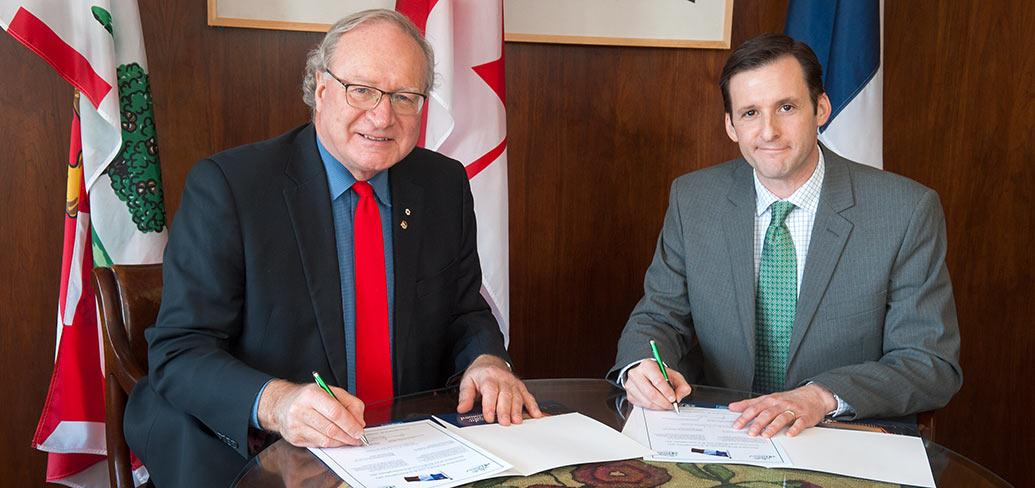 Premier MacLauchlan and Jese Francis sitting at a desk signing documents.
