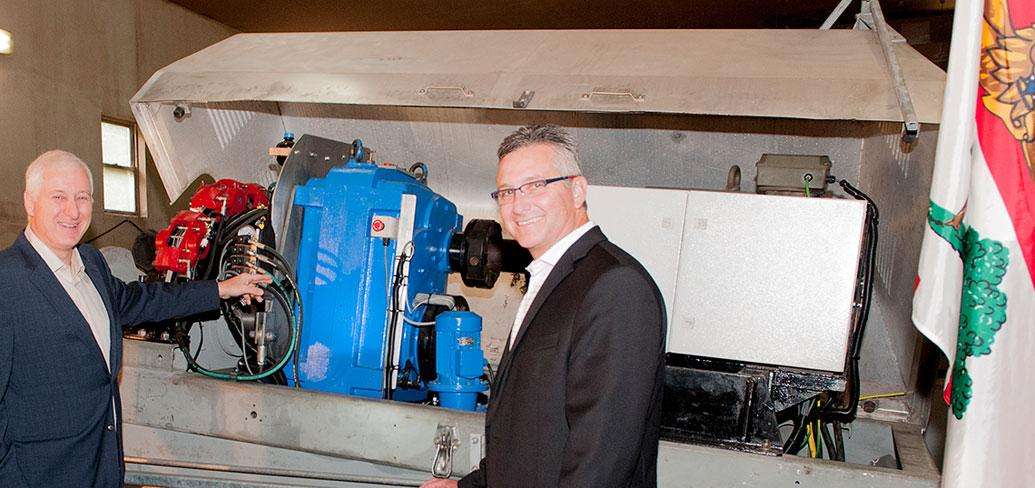 Minister MacDonald and Carl Brothers stand in front of wind trubine machinery under production.