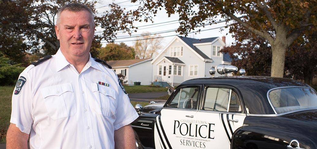 Photo shows Gary McGuigan standing next to Charlottetown Police Services' classic patrol car.