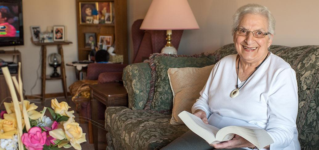 Photos shows Gladys Dirani sitting in her living room with a book on her lap.