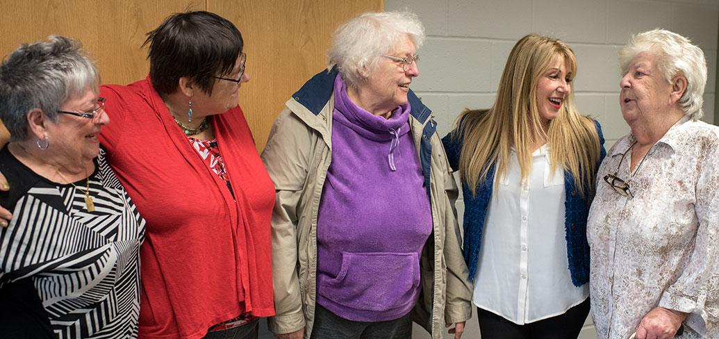 Photos shows Minister Tina Mundy standing with four senior ladies.