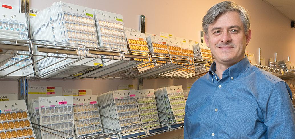 Photo shows Grant Wyand standing next to rows of medications