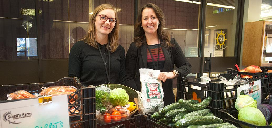 Two women facing the camera standing behind a display of fresh vegetables.