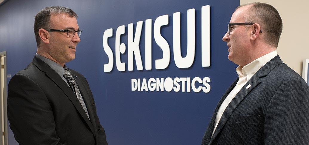 Two people standing in front of a sign at Sekisui Diagnostics