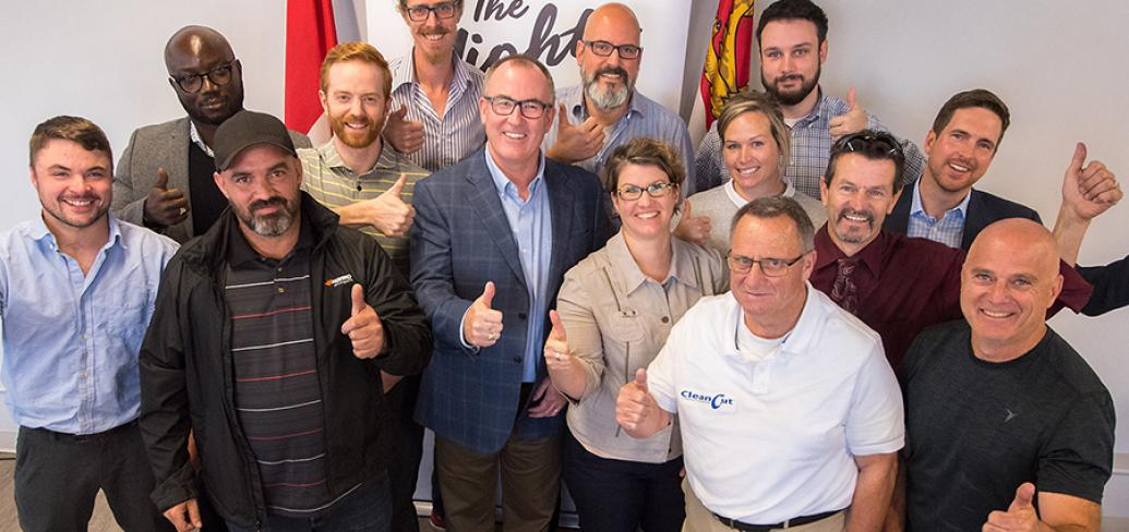 A large group of business people - recipients of the 2018 Ignition Fund - stand giving thumbs up.