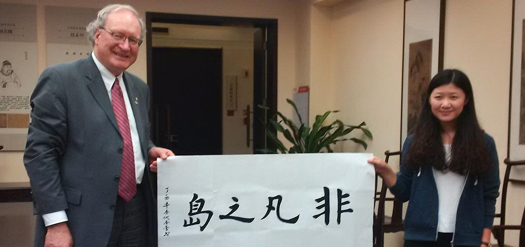 Premier MacLauchlan and  Chinese steundent hold a banner saying The Might Island in Chinese calligraphy