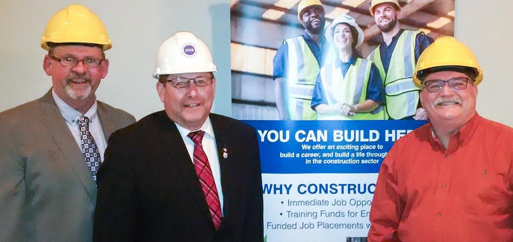 Three people standing beside each other wearing hard hats and a banner sign is behind them