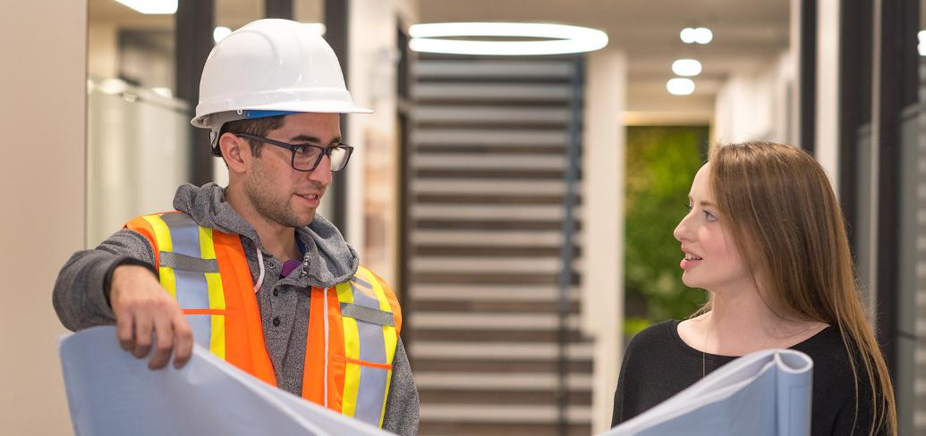 Two people, ne with a hardhat on, holding drafting documents while in a hallays.